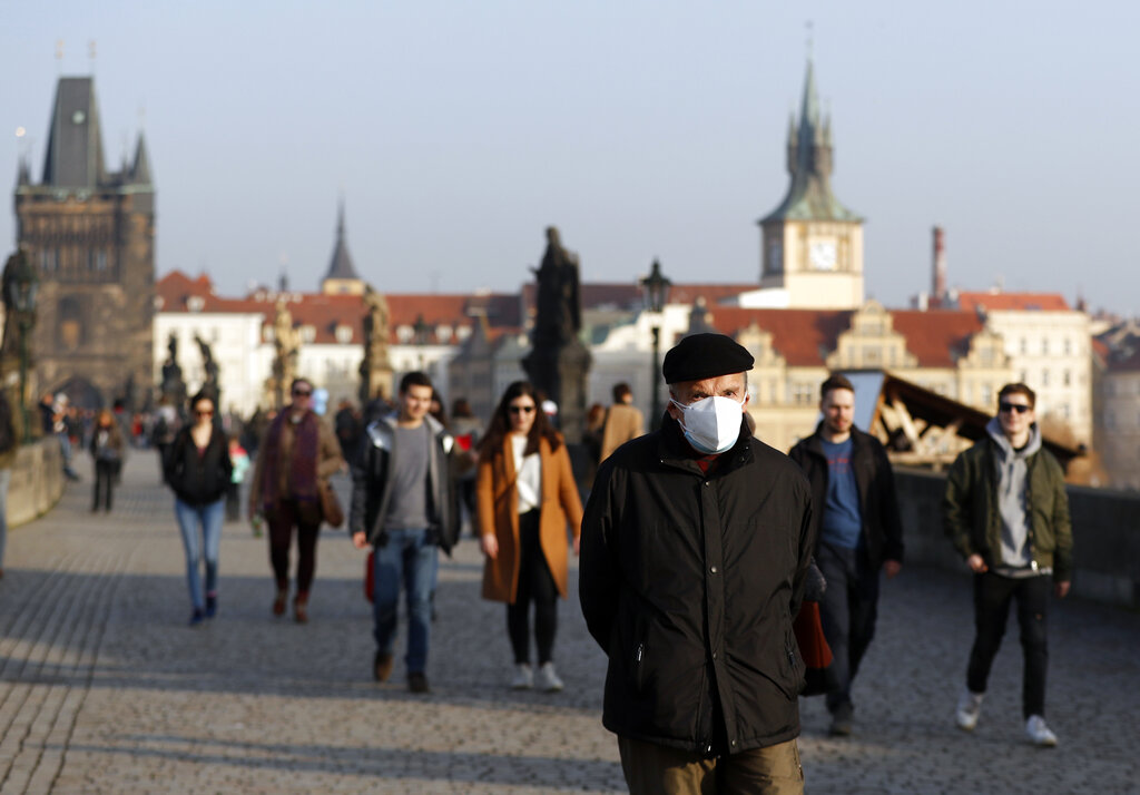 In this Thursday, Feb. 25, 2021 file photo, a man wearing a face mask walks across the medieval Charles Bridge in Prague, Czech Republic. (AP Photo/Petr David Josek, File)