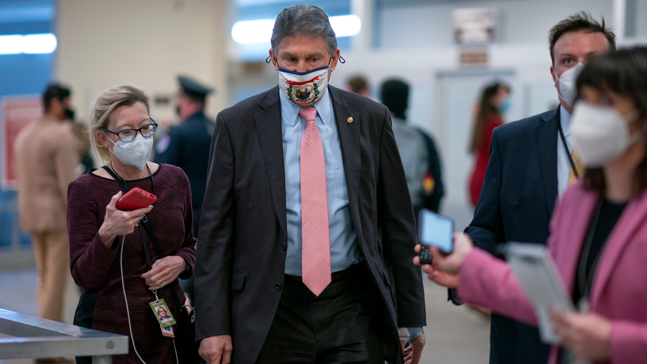 In this Feb. 25, 2021, file photo, reporters question Sen. Joe Manchin, D-W.Va., as he arrives for votes on President Joe Biden's cabinet nominees, at the Capitol in Washington. (AP Photo/J. Scott Applewhite, File)