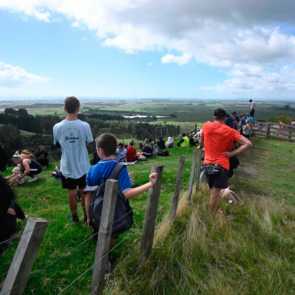 People watch for signs of a tsunami from a hill above Papamoa Beach, New Zealand, as a tsunami warning is issued on March 5, 2021. (George Novak / New Zealand Herald via Associated Press)