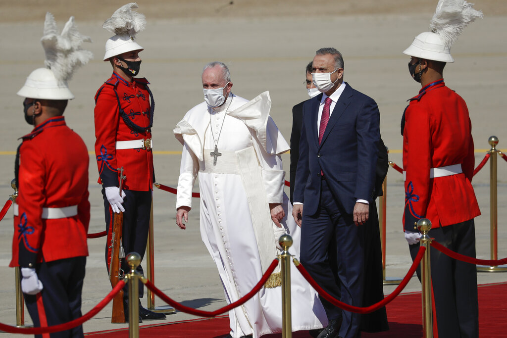 Pope Francis is flanked by Iraqi Prime Minister Mustafa al-Kadhimi upon his arrival at Baghdad's international airport, Iraq, Friday, March 5, 2021. (AP Photo/Andrew Medichini)