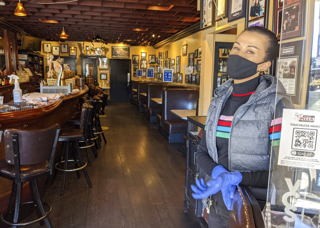 Ro Hart, an assistant general manager and hostess at Tony's Pizza Napoletana in San Francisco stands in front of a totally empty indoors seating area during the lunch hour on Thursday, March 4, 2021. (AP Photo/Mike Liedtke)