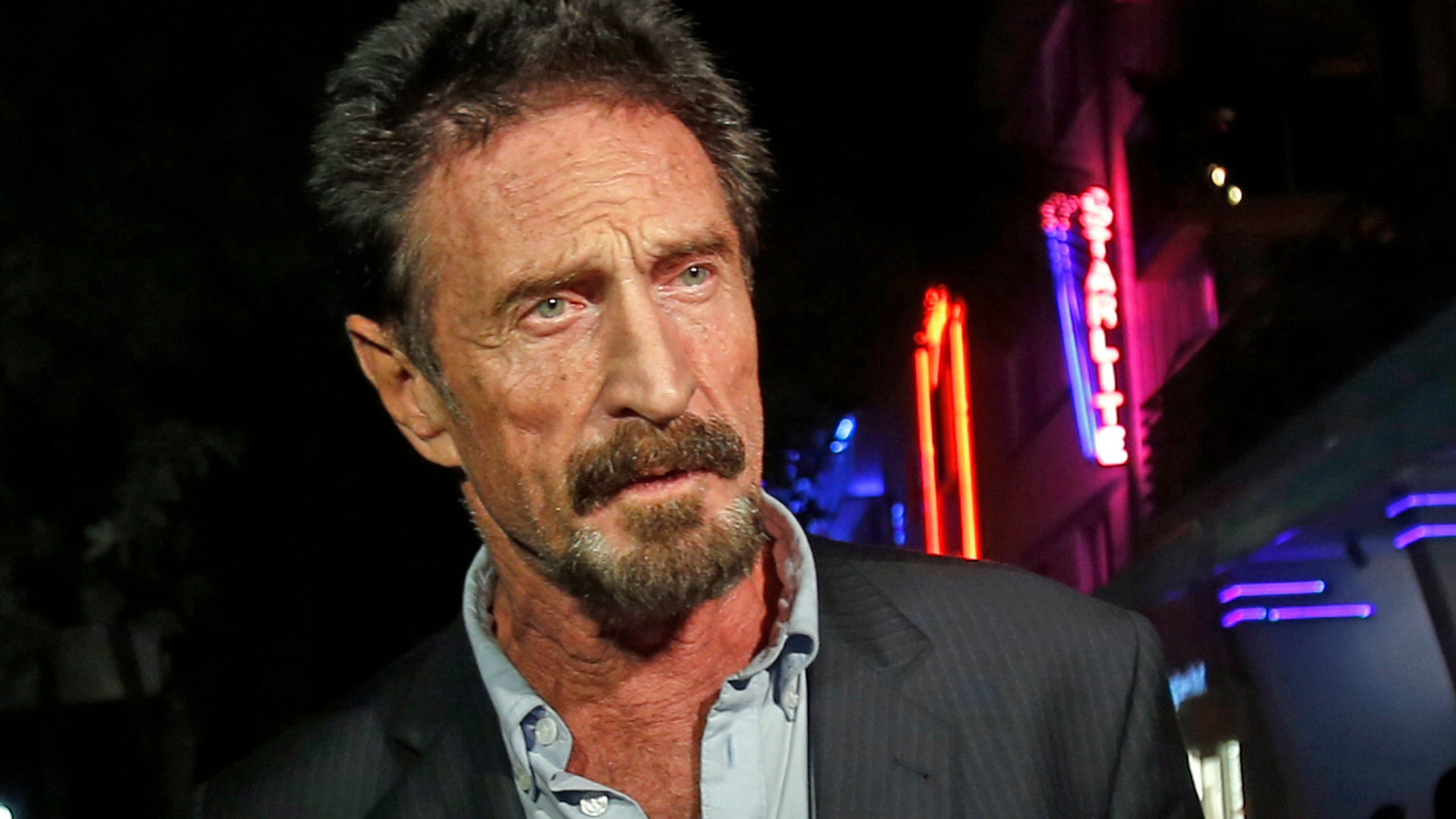 In this Dec. 12, 2012 file photo, anti-virus software founder John McAfee answers questions to reporters as he walks on Ocean Drive, in the South Beach area of Miami Beach, Fla. (AP Photo/Alan Diaz, File)