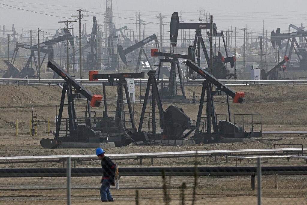 In this Jan. 16, 2015, file photo, a person walks past pump jacks operating at the Kern River Oil Field in Bakersfield, Calif. (AP Photo/Jae C. Hong, File)