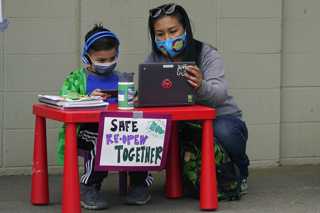 In this Thursday, Feb. 18, 2021, file photo, Maya Peralta, right, sits with her son, Clarendon Alternative Elementary School second-grader H Suchovsky, as students and parents attend distance learning Zoom classes at Midtown Terrace Playground in San Francisco. (AP Photo/Jeff Chiu, File)