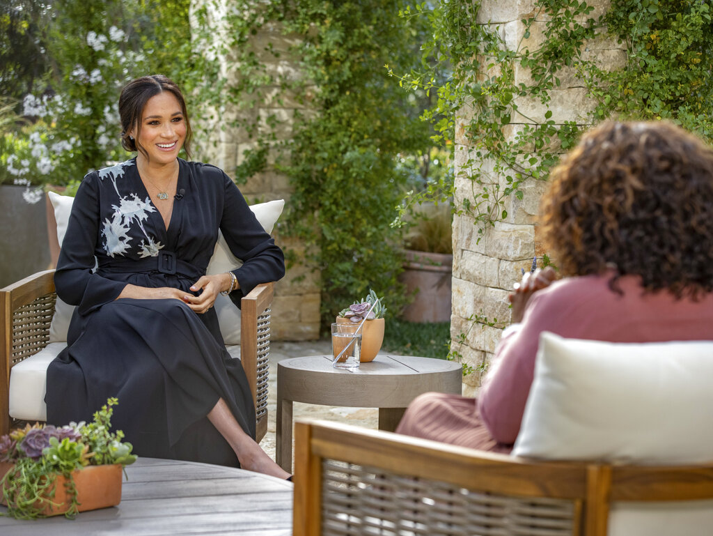 This image provided by Harpo Productions shows Prince Harry, left, and Meghan, Duchess of Sussex, speaking about expecting their second child during an interview with Oprah Winfrey. (Joe Pugliese/Harpo Productions via AP)