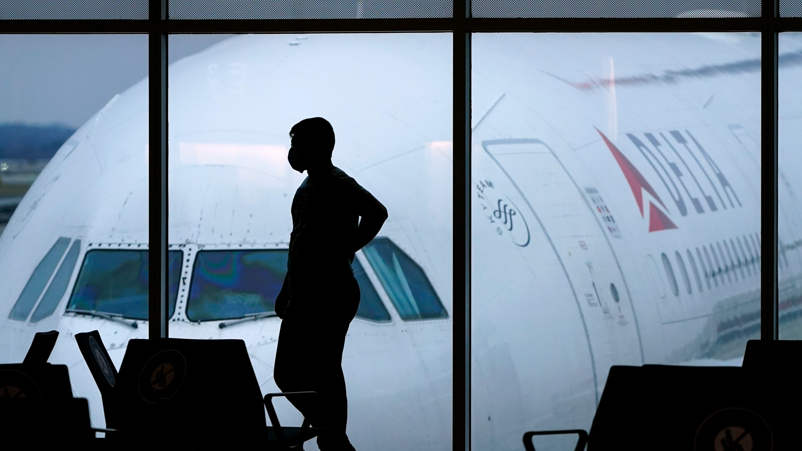 In this Feb. 18, 2021 file photo, a passenger wears a face mask to help prevent against the spread of the coronavirus as he waits for a Delta Airlines flight at Hartsfield-Jackson International Airport in Atlanta. (AP Photo/Charlie Riedel, File)