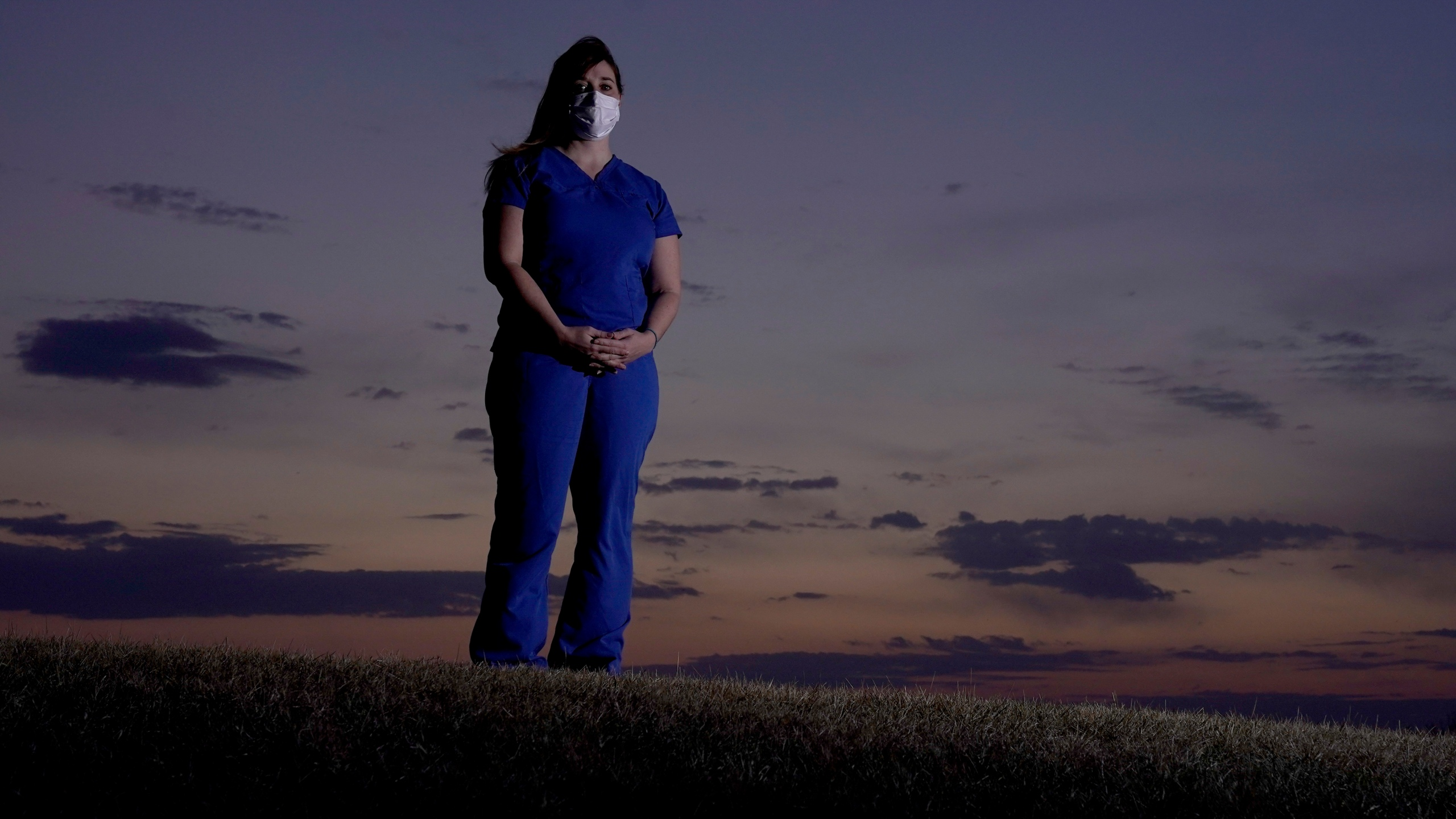 Emergency room nurse L'Erin Ogle stands at dawn before starting her 12-hour shift at a nearby hospital Tuesday, March 9, 2021, in Overland Park, Kan. (AP Photo/Charlie Riedel)