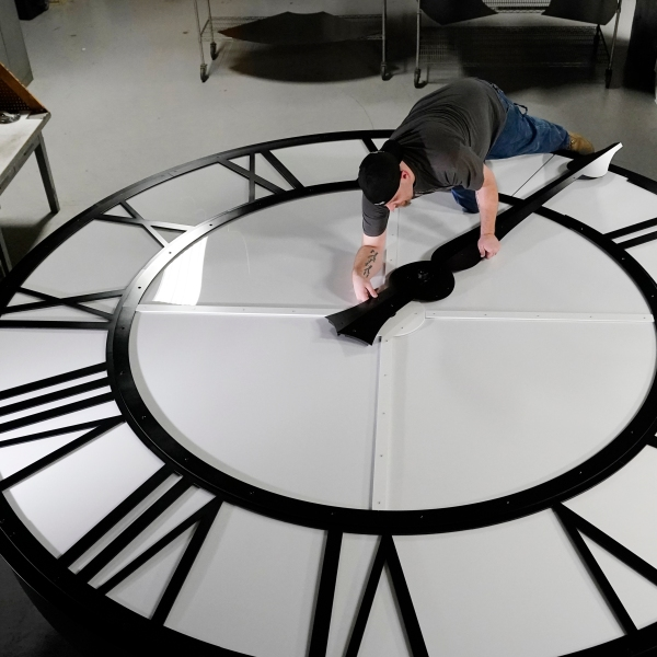 Electric Time technician Dan LaMoore puts a clock hand onto a 1000-lb., 12-foot diameter clock constructed for a resort in Vietnam, Tuesday, March 9, 2021, in Medfield, Mass. Daylight saving time begins at 2 a.m. local time Sunday, March 14, 2021, when clocks are set ahead one hour. (AP Photo/Elise Amendola)