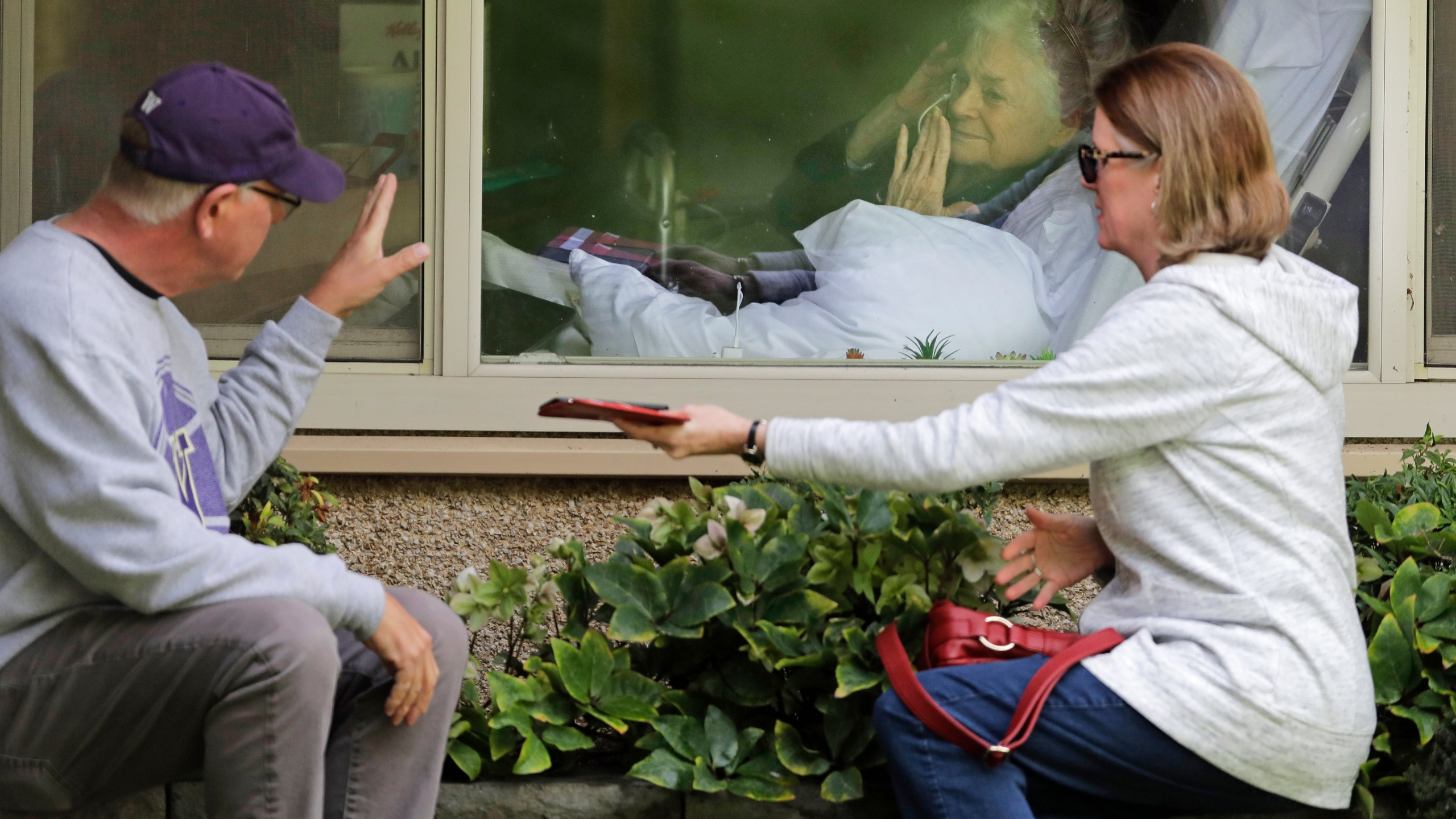 Judie Shape, center, who has tested positive for the coronavirus, blows a kiss to her son-in-law, Michael Spencer, left, as Shape's daughter, Lori Spencer, right, looks on, as they visit on the phone and look at each other through a window at the Life Care Center in Kirkland, Wash., on March 11, 2020. (Ted S. Warren / Associated Press)