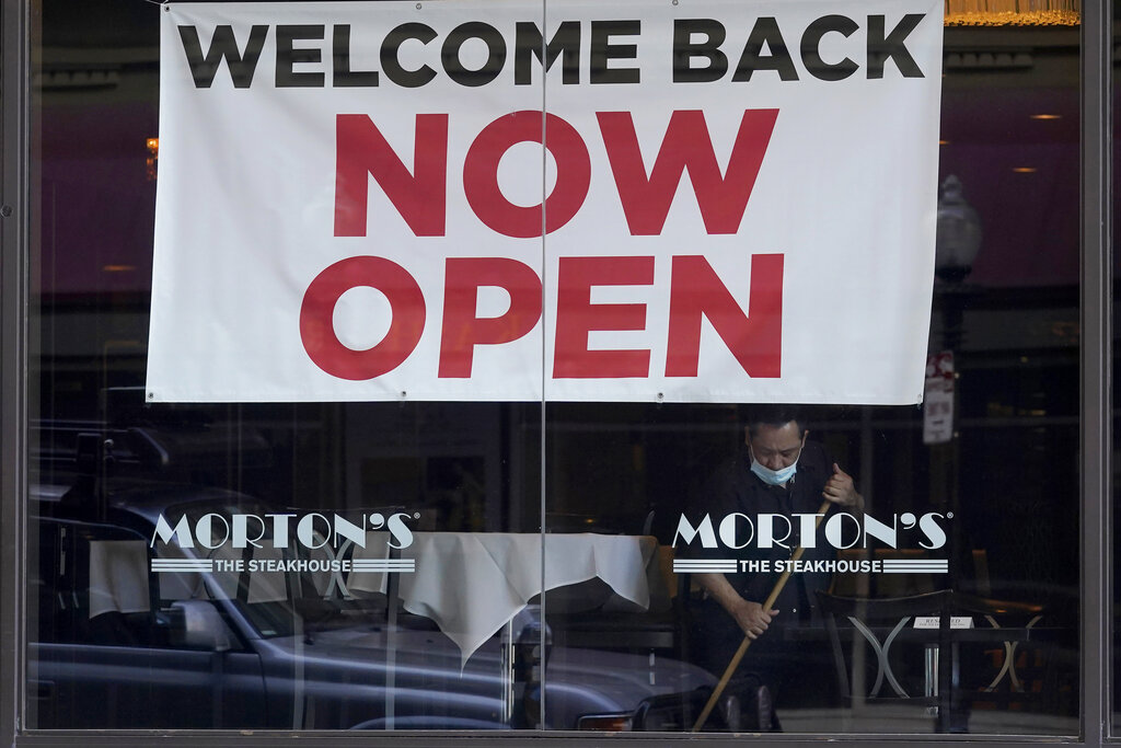 """In this March 4, 2021, file photo, a sign reading """"Welcome Back Now Open"""" is posted on the window of a Morton's Steakhouse restaurant as a man works inside during the coronavirus pandemic in San Francisco. (AP Photo/Jeff Chiu, File)"""