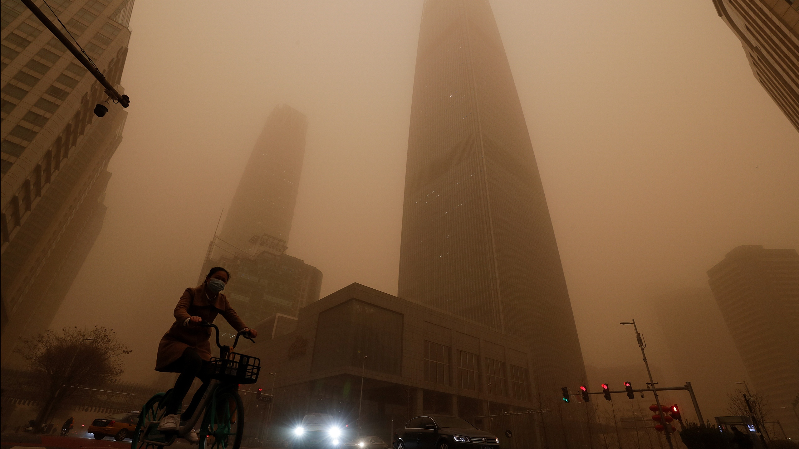 A cyclist and motorists move past office buildings amid a sandstorm during the morning rush hour in the central business district in Beijing, Monday, March 15, 2021. (AP Photo/Andy Wong)