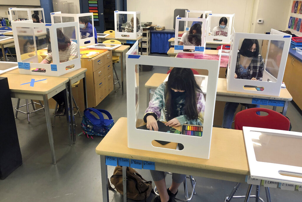 In this March 2, 2021, file photo, socially distanced, and with protective partitions, students work on an art project during class at the Sinaloa Middle School in Novato, California. (AP Photo/Haven Daley, File)