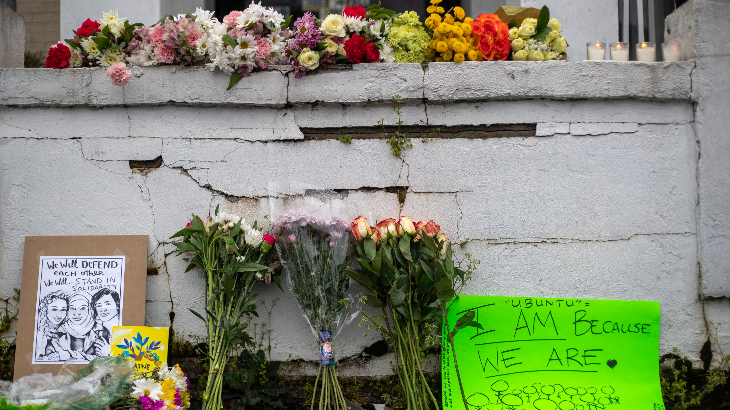 Flowers and signs are displayed at a makeshift memorial outside of the Gold Spa in Atlanta, Wednesday, March 17, 2021. (Alyssa Pointer/Atlanta Journal-Constitution via AP)