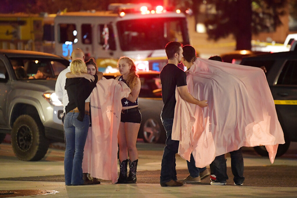 In this Thursday, Nov. 8, 2018, file photo, people comfort each other as they stand near the scene in Thousand Oaks, Calif. (AP Photo/Mark J. Terrill)