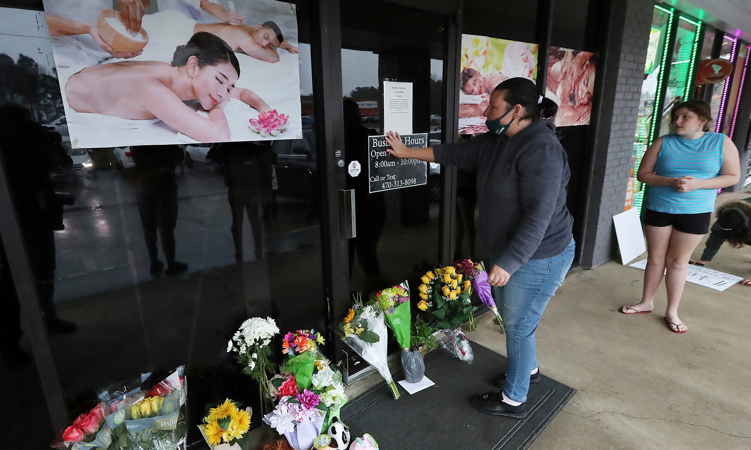 In this March 17, 2021, file photo, Jessica Lang pauses and places her hand on the door in a moment of grief after dropping off flowers with her daughter Summer at Youngs Asian Massage parlor where four people were killed in Acworth, Ga. (Curtis Compton/Atlanta Journal-Constitution via AP, File)