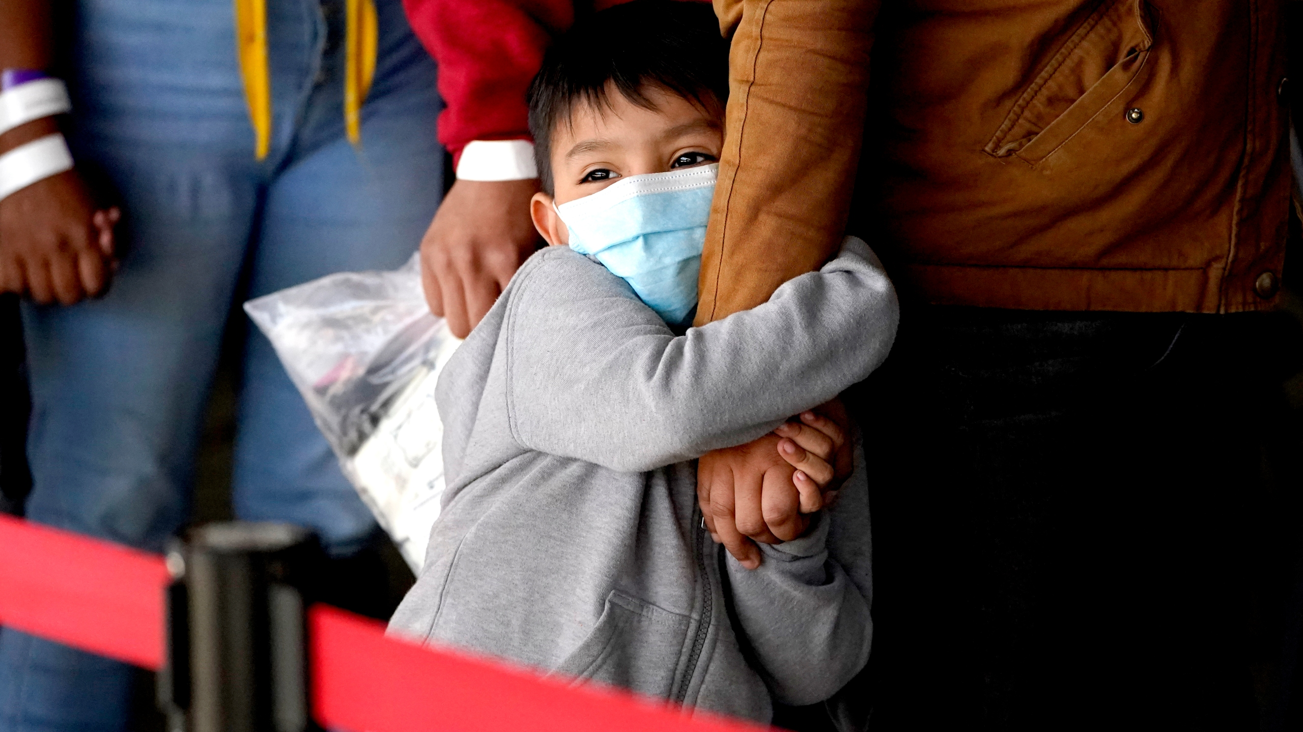 A migrant child holds onto a woman's arm as they wait to be processed by a humanitarian group after being released from U.S. Customs and Border Protection custody at a bus station, Wednesday, March 17, 2021, in Brownsville, Texas. (AP Photo/Julio Cortez)