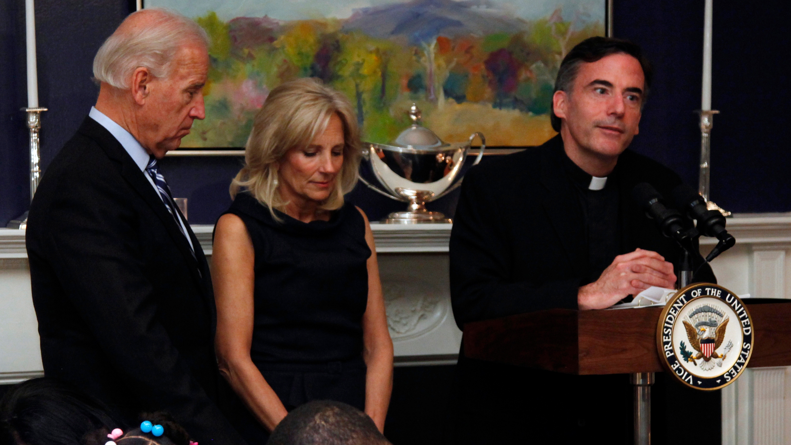 In this Nov. 22, 2010 file photo, then Vice President Joe Biden and his wife, Jill Biden stand with heads bowed as the Rev. Kevin O'Brien says the blessing during a Thanksgiving meal for Wounded Warriors in Washington. (Carolyn Kaster/Associated Press)