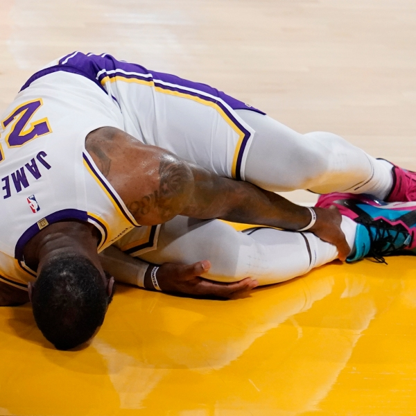 Los Angeles Lakers forward LeBron James holds his ankle after going down with an injury during the first half of an NBA basketball game against the Atlanta Hawks on March 20, 2021, in Los Angeles. (AP Photo/Marcio Jose Sanchez)