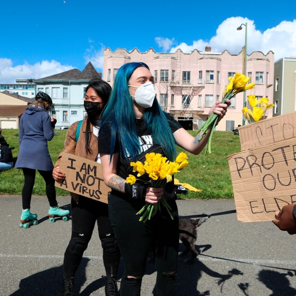 Organizer Ashley Silva distributes flowers to folks attending a rally organized in solidarity against racist violence against Asian Americans at Madison Park on March 20, 2021, in Oakland, Calif. (Yalonda M. James/San Francisco Chronicle via AP)