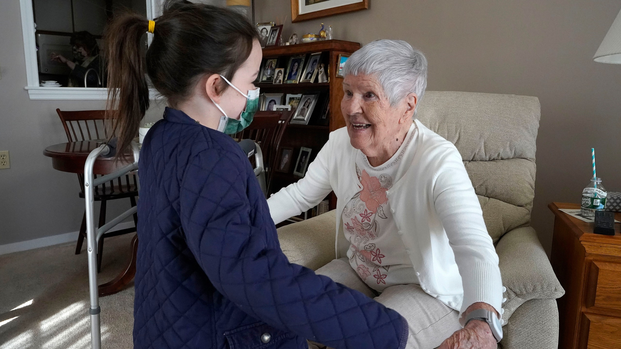 Eileen Quinn, 98, right, a resident at New Pond Village retirement community in Walpole, Mass., greets her great-granddaughter Maeve Whitcomb, 6, at the retirement community in Walpole on March 21, 2021. (Steven Senne/Associated Press)