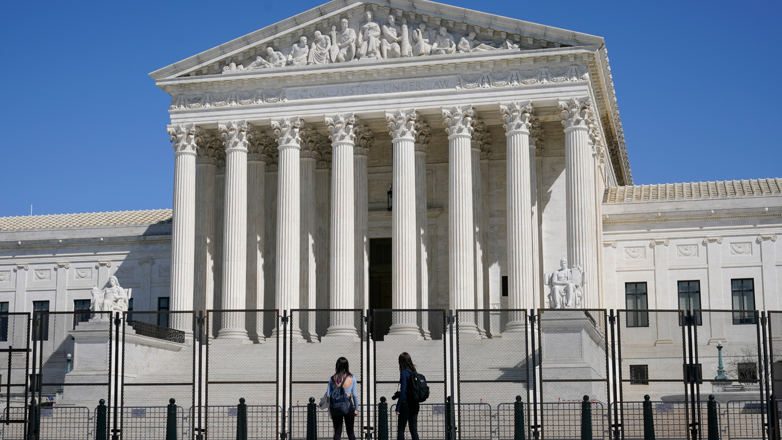 People view the Supreme Court building from behind security fencing on March 21, 2021. (Patrick Semansky/Associated Press)