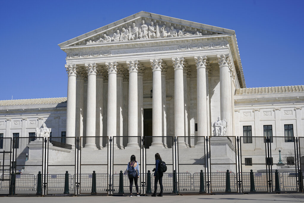 People view the Supreme Court building from behind security fencing on Capitol Hill in Washington, Sunday, March 21, 2021, after portions of an outer perimeter of fencing were removed overnight to allow public access. (AP Photo/Patrick Semansky)