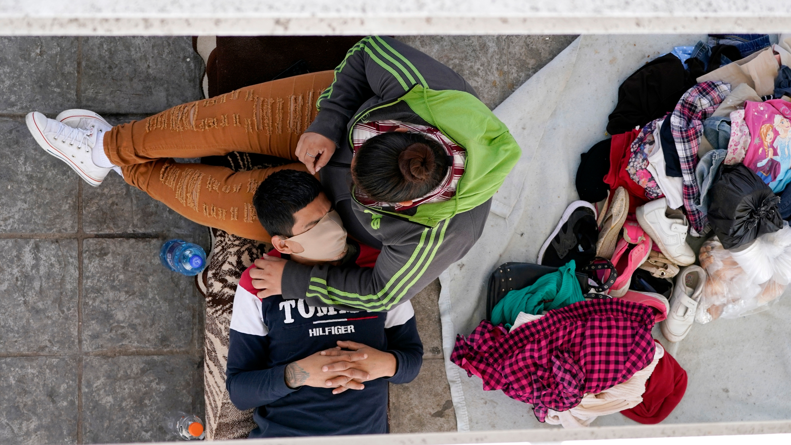Migrants who were caught trying to cross into the U.S. and were deported rest under a ramp that leads to the McAllen-Hidalgo International Bridge in Reynosa, Mexico, on March 18, 2021. (Julio Cortez / Associated Press)