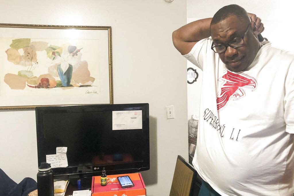 Armetrius Neason poses for a photo inside his room at the Efficiency Lodge hotel outside Atlanta on March 16, 2021. (AP Photo/Sudhin S. Thanawala)