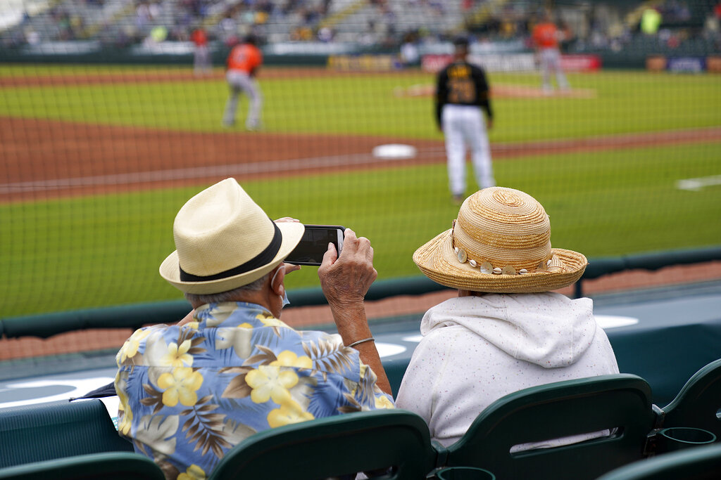 In this Monday, March 22, 2021 file photo, two older adults socially distanced, watch a spring training exhibition baseball game between the Pittsburgh Pirates and the Baltimore Orioles in Bradenton, Fla. (AP Photo/Gene J. Puskar, File)