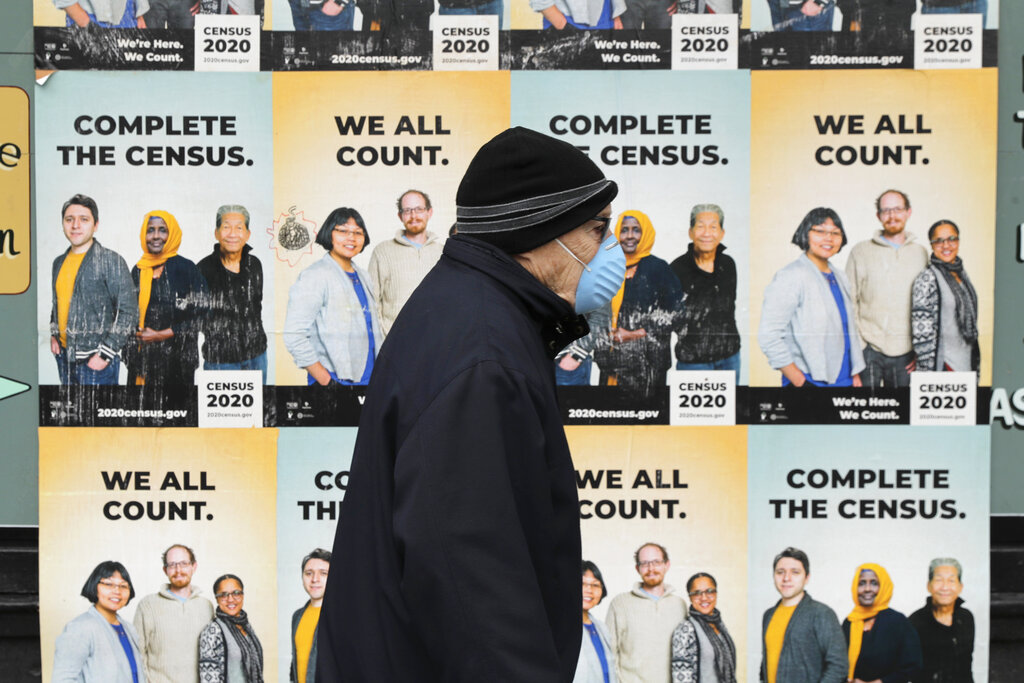 In this April 1, 2020, file photo, a man wearing a mask walks past posters encouraging participation in the 2020 Census in Seattle's Capitol Hill neighborhood. (AP Photo/Ted S. Warren, File)