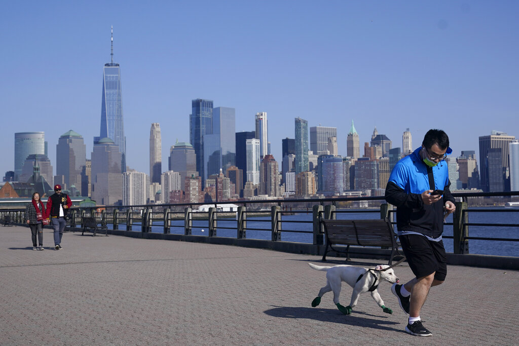In this March 9, 2021, file photo, people enjoy the warming weather and a view of lower Manhattan at Liberty State Park in Jersey City, N.J. (AP Photo/Seth Wenig, File)