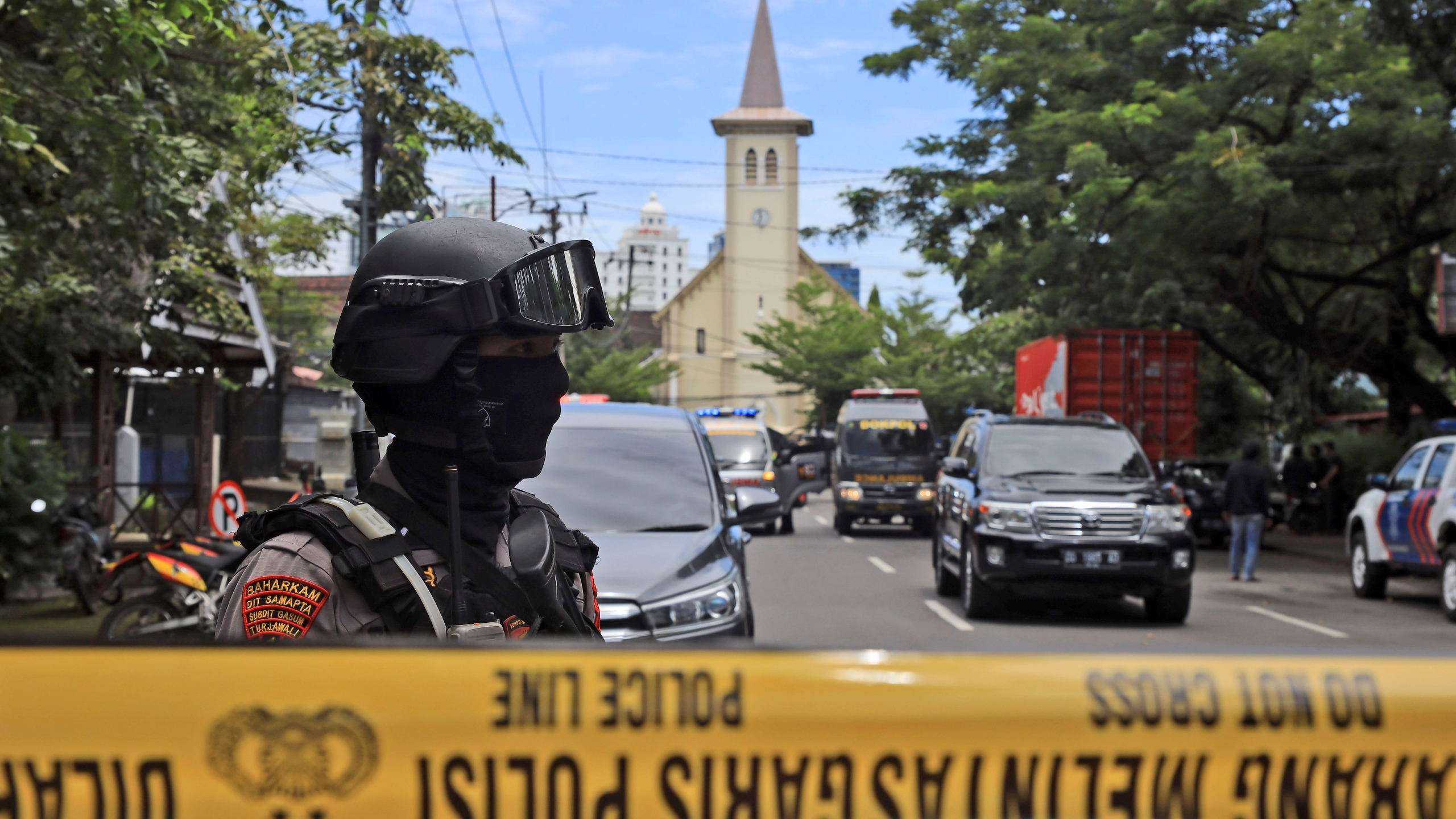 A police officer stands guard near a church where an explosion went off in Makassar, South Sulawesi, Indonesia, Sunday, March 28, 2021. (AP Photo/Yusuf Wahil)