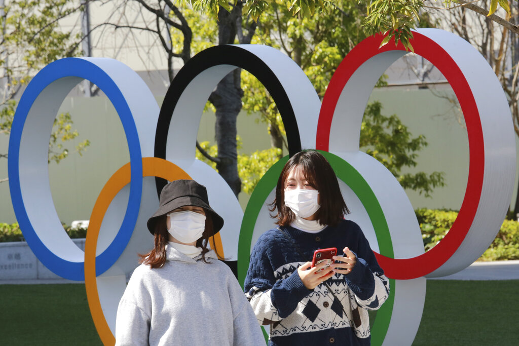 In this March 17, 2021, file photo, people walk past the Olympic rings in Tokyo. The Tokyo Olympics open in under four months, and the torch relay has begun to crisscross Japan with 10,000 runners. (AP Photo/Koji Sasahara)