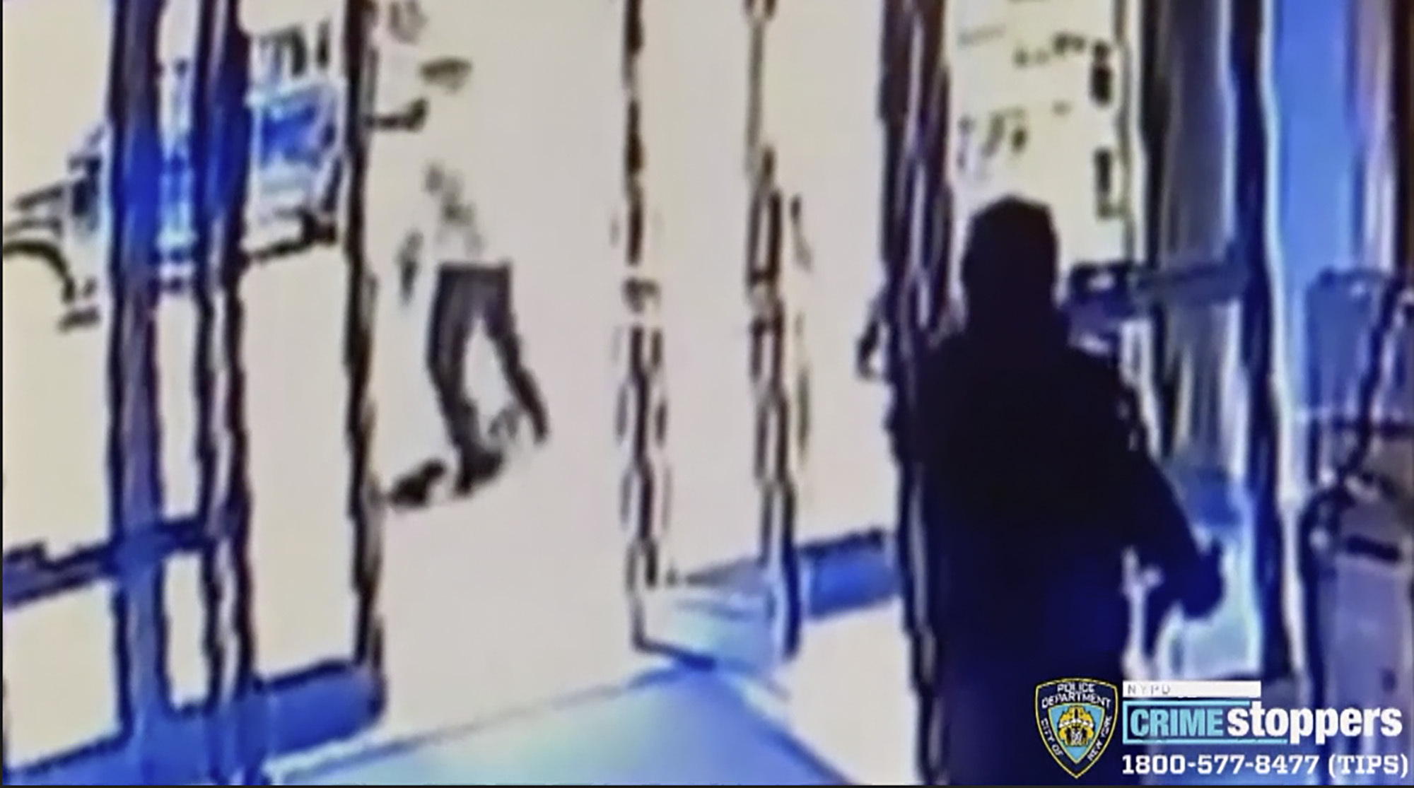 This image taken from surveillance video provided by the New York City Police Department shows a person of interest, background center, assaulting an Asian American woman, on ground, on March 29, 2021, in New York.