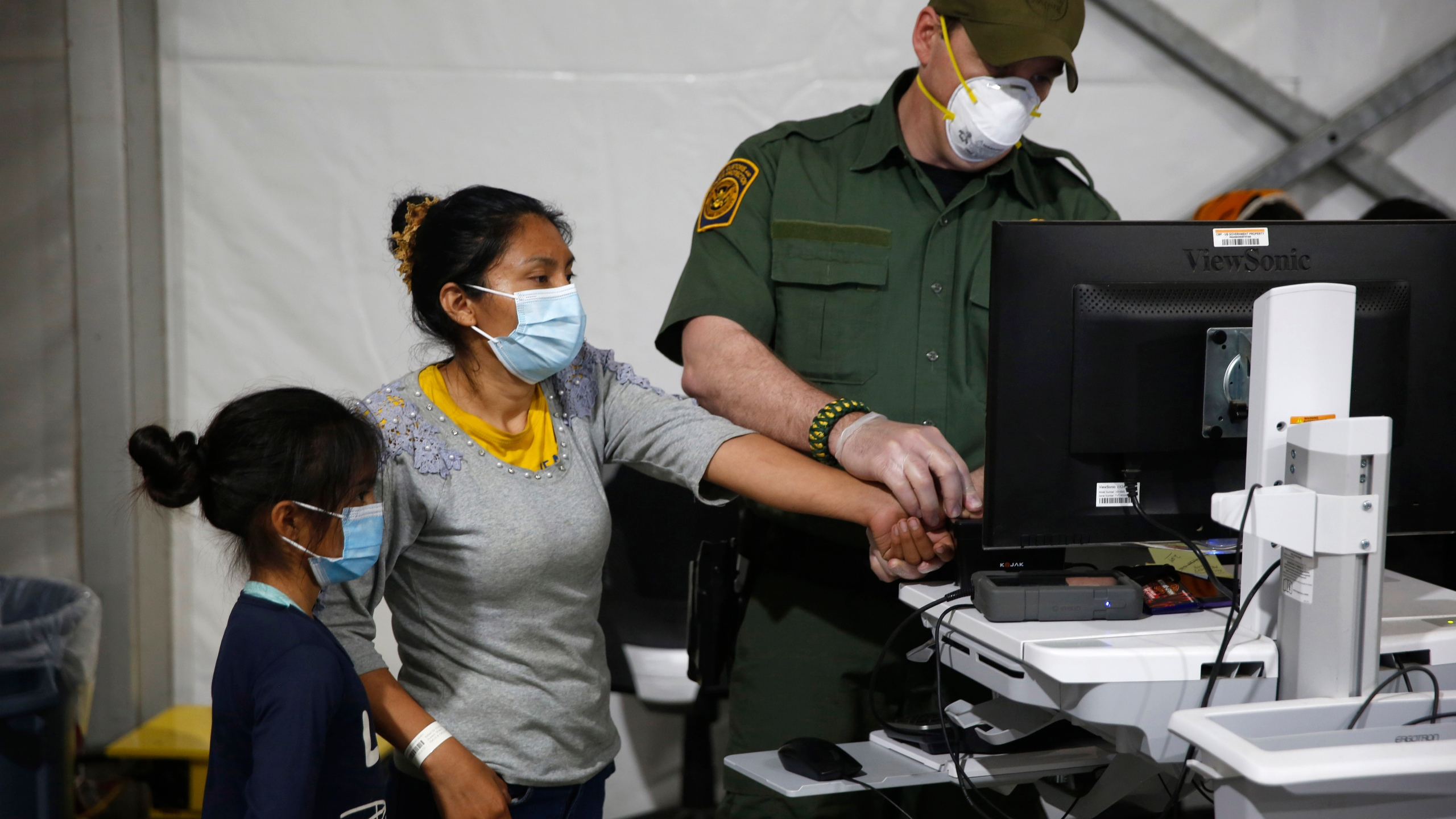 A migrant and her daughter have their biometric data entered at the intake area of the Donna Department of Homeland Security holding facility, the main detention center for unaccompanied children in the Rio Grande Valley, in Donna, Texas, on March 30, 2021. (AP Photo/Dario Lopez-Mills, Pool)