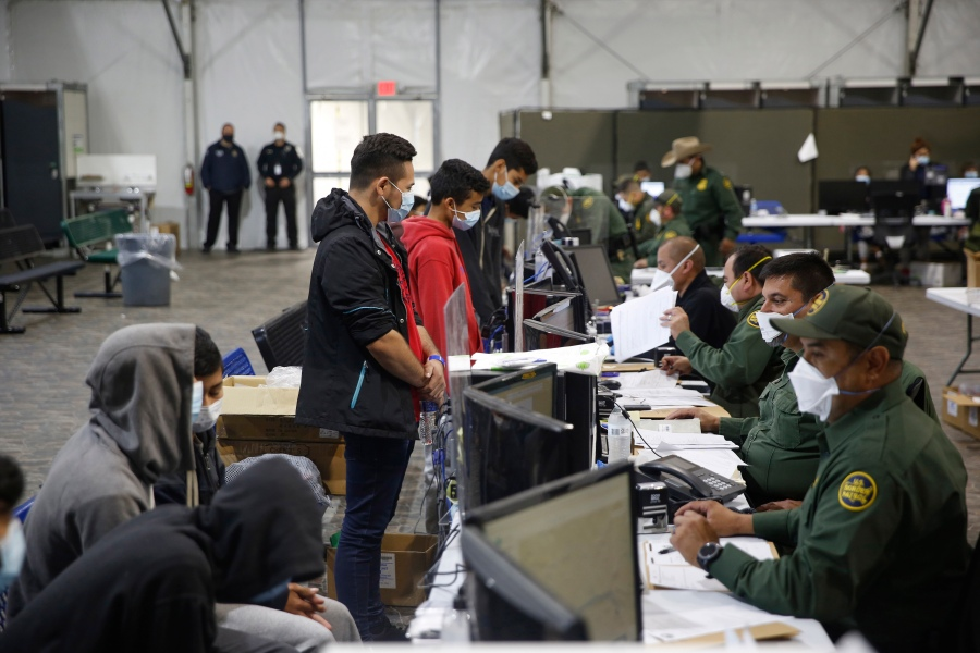 Migrants are processed at the intake area of the Donna Department of Homeland Security holding facility, the main detention center for unaccompanied children in the Rio Grande Valley, in Donna, Texas, on March 30, 2021. (AP Photo/Dario Lopez-Mills,Pool)