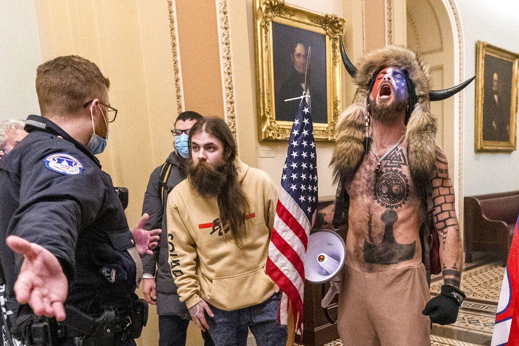 In this Wednesday, Jan. 6, 2021 file photo, supporters of President Donald Trump, including Jacob Chansley, right with fur hat, are confronted by U.S. Capitol Police officers outside the Senate Chamber inside the Capitol in Washington. (AP Photo/Manuel Balce Ceneta, File)