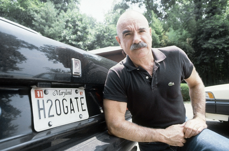 G. Gordon Liddy poses by the back of his car near his home in Fort Washington, Md. on Aug. 16, 1987. (Ira Schwarz/Associated Press)