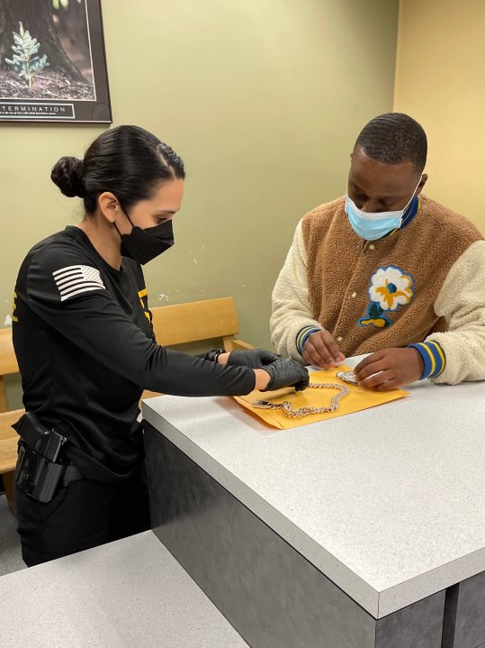 An officer returns jewelry to a victim of a brazen armed robbery. (LAPD)