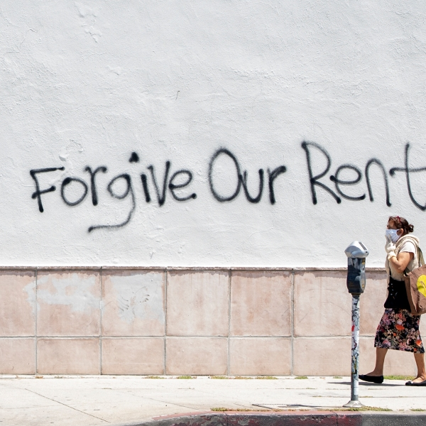 A woman wearing a mask walks past a wall bearing a graffiti asking for rent forgiveness on La Brea Ave on National May Day amid the Covid-19 pandemic, May 1, 2020, in Los Angeles, California. (Photo by VALERIE MACON/AFP via Getty Images)