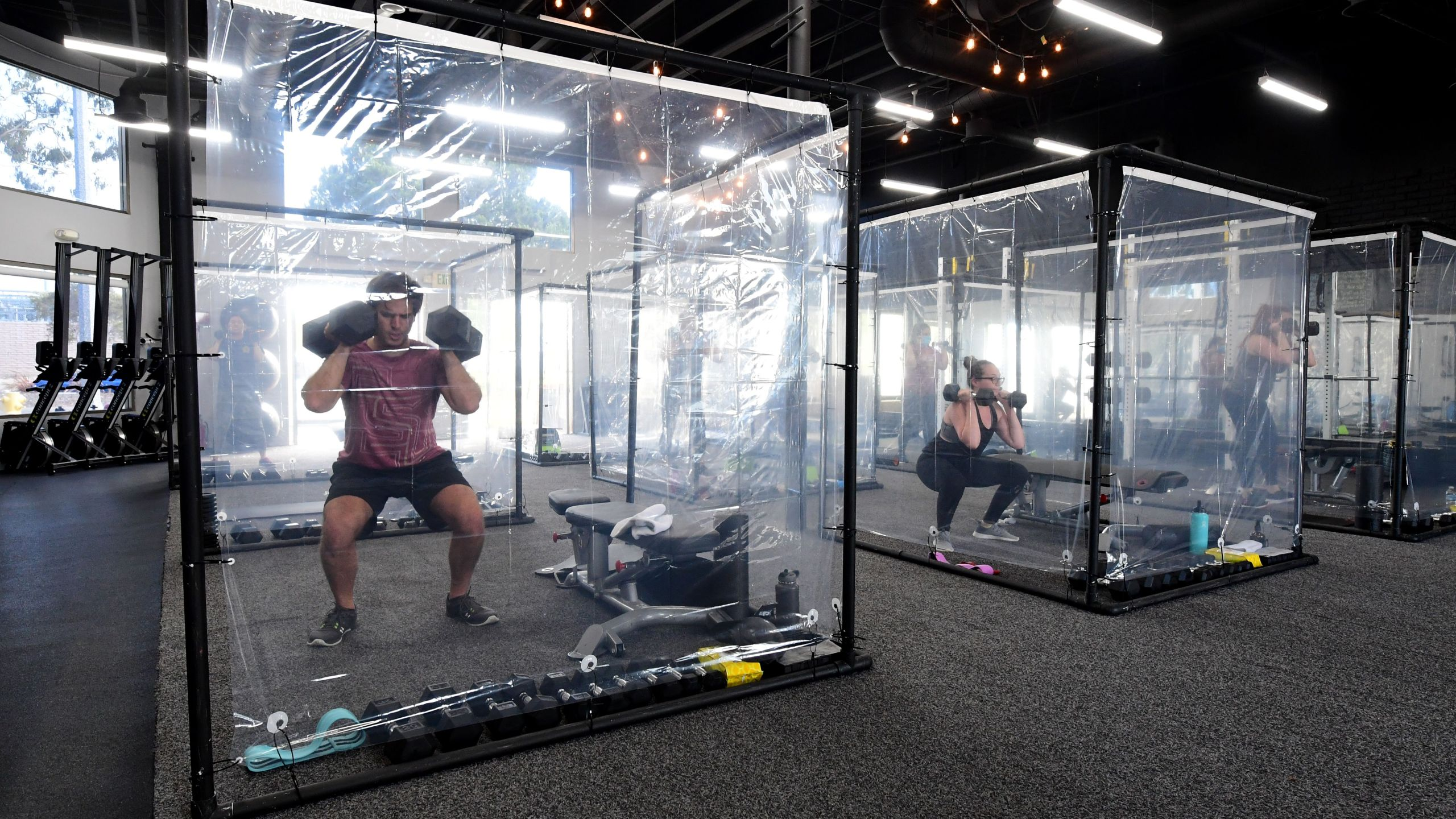 People exercise at Inspire South Bay Fitness behind plastic sheets in their workout pods on June 15, 2020, in Redondo Beach, California. (FREDERIC J. BROWN/AFP via Getty Images)