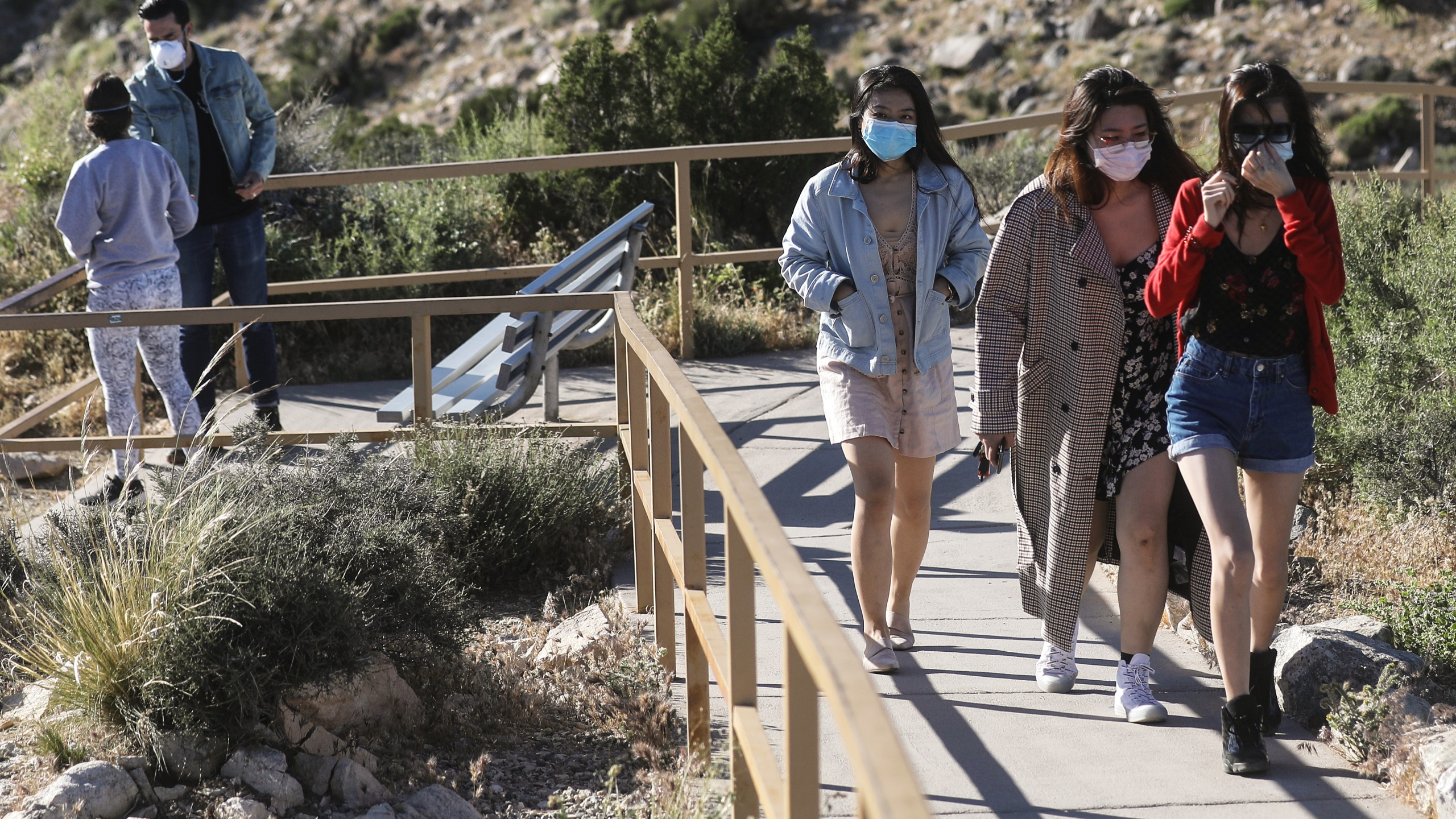 Visitors wear face masks on a walking path in Joshua Tree National Park one day after the park reopened after being closed for two months due to the coronavirus pandemic on May 18, 2020. (Mario Tama/Getty Images)