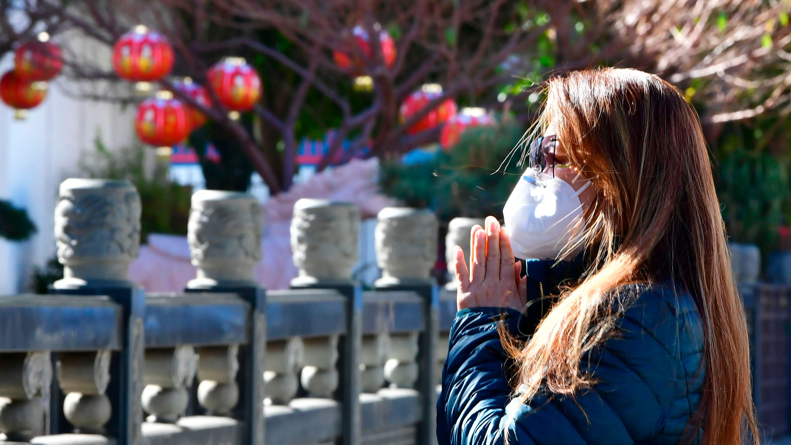 A woman prays on the first day of the Lunar New Year of the Ox outside the Thien Hau Temple, temporarily closed due to the coronavirus pandemic, in the Chinatown neighborhood of Los Angeles, California on February 12, 2021. (Photo by Frederic J. BROWN / AFP) (Photo by FREDERIC J. BROWN/AFP via Getty Images)