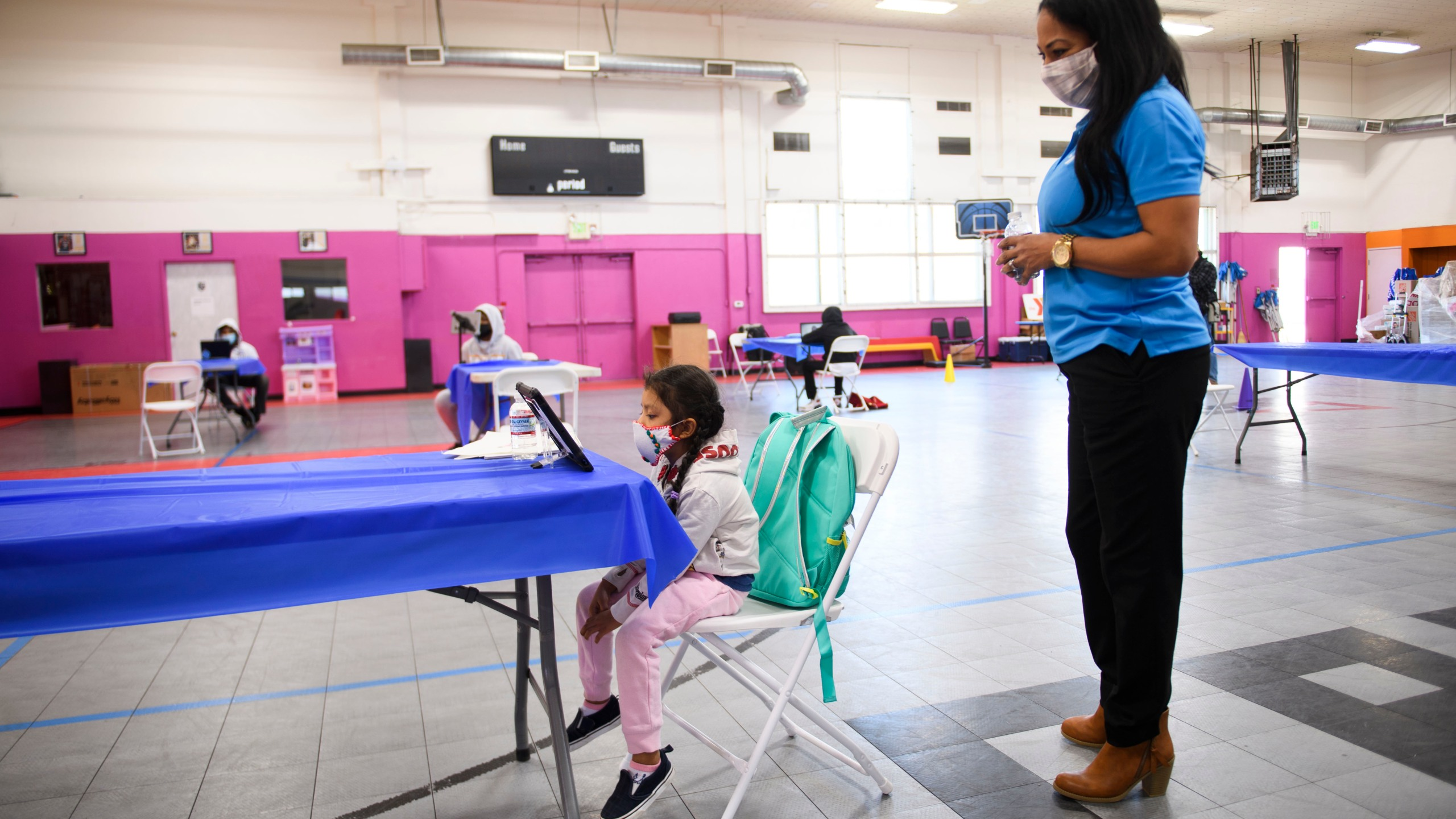 A YMCA staff member assists a child as they attend online classes at a learning hub inside the Crenshaw Family YMCA during the Covid-19 pandemic on February 17, 2021 in Los Angeles, California. (PATRICK T. FALLON/AFP via Getty Images)
