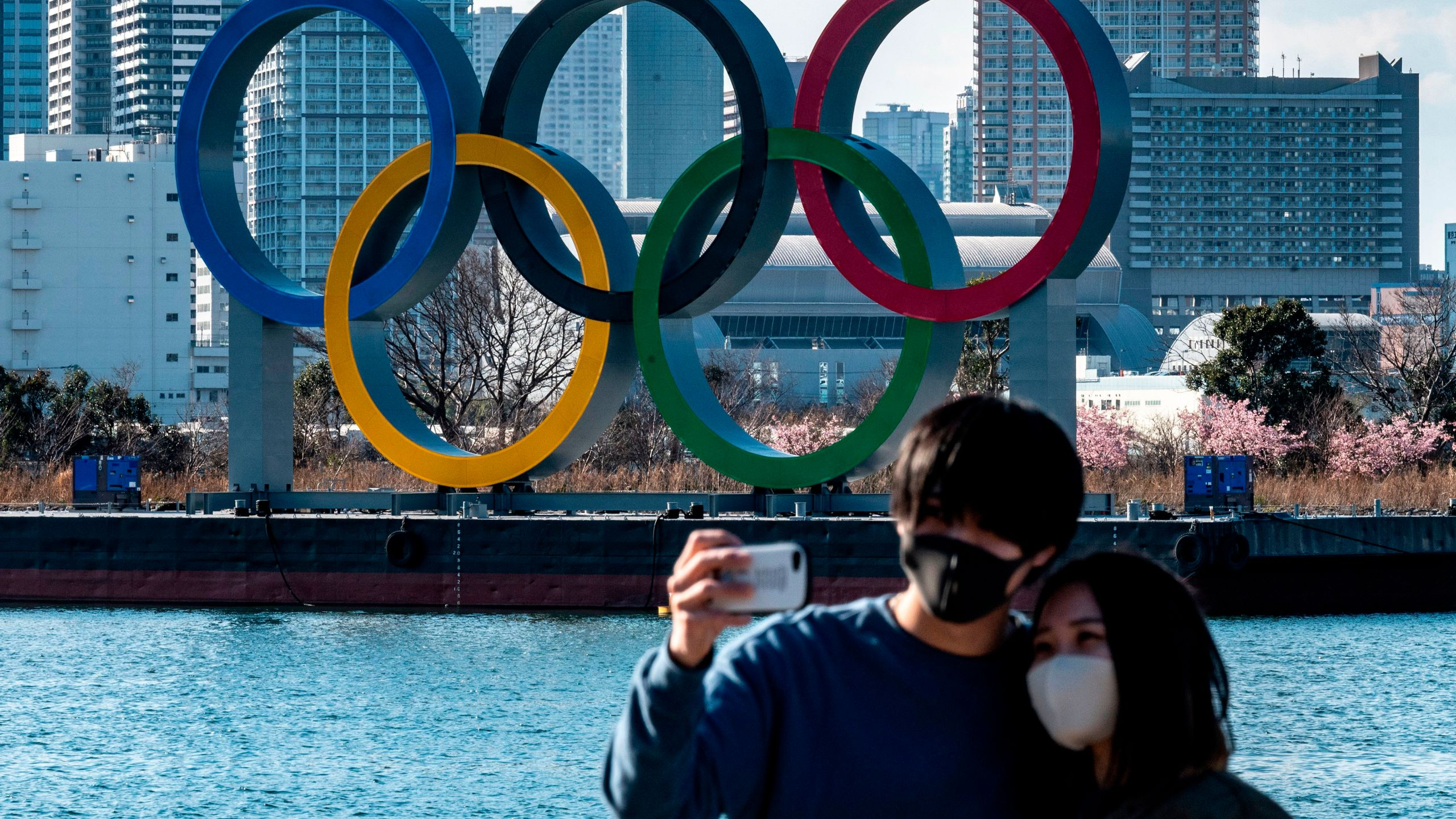 A couple pose for photos in front of the Olympic rings on display at the Odaiba waterfront in Tokyo on Feb. 24, 2021. (PHILIP FONG/AFP via Getty Images)