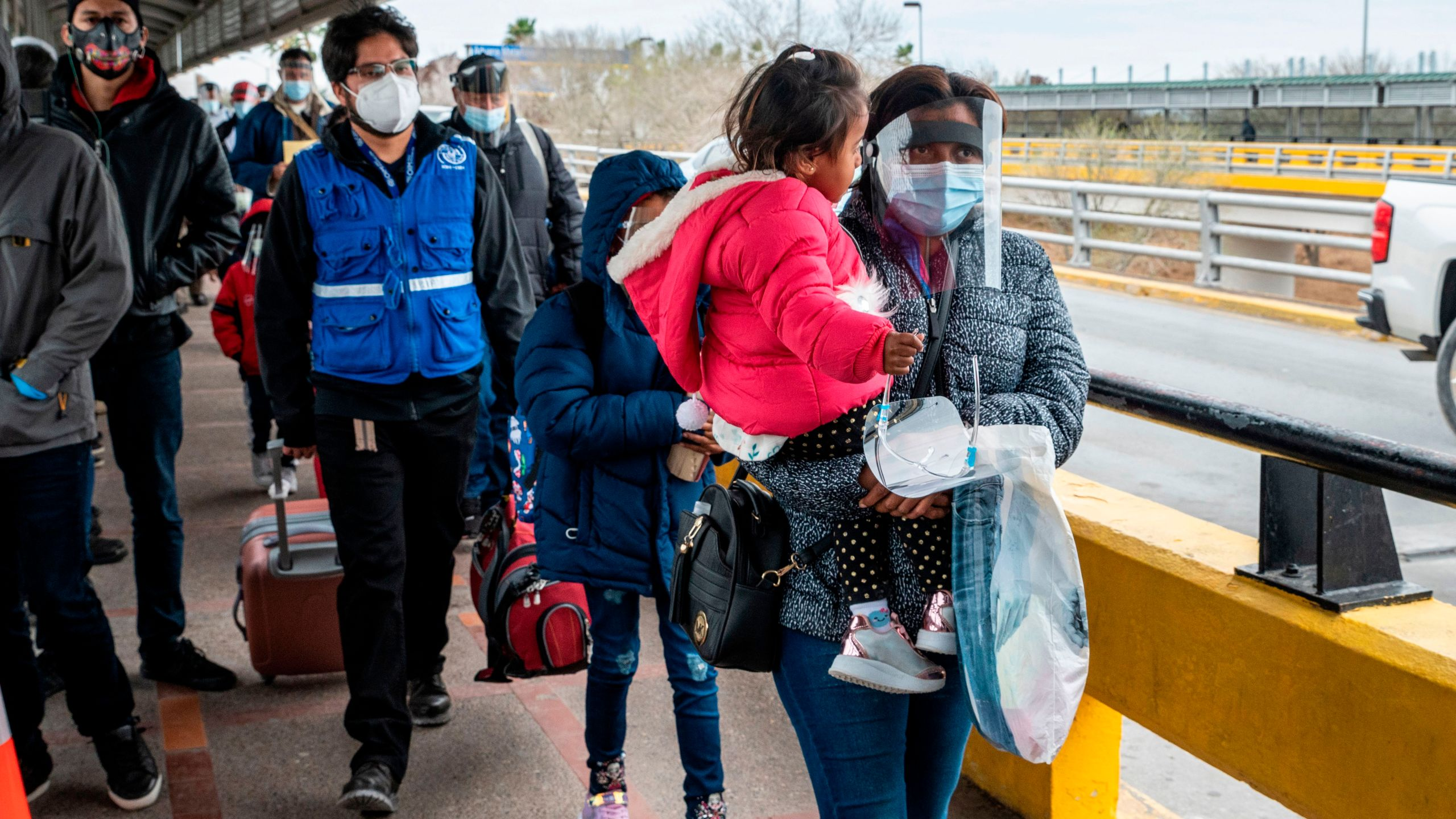 A migrant family approaches the US border on Gateway International Bridge in Brownsville, Texas on March 2, 2021. (SERGIO FLORES/AFP via Getty Images)