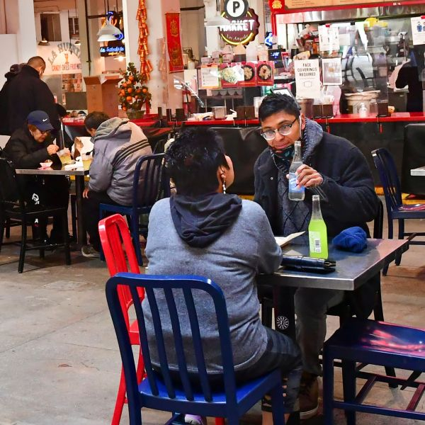 People enjoy lunch at Grand Central Market as indoor dining reopens in Los Angeles, on March 15, 2021. Los Angeles and Southern California is allowed to partially reopen indoor dining and movie theaters Governor Gavin Newsom announced last week, as the region hit key health criteria. Slammed by a brutal COVID-19 pandemic winter spike, California has seen a rapid decline in infection rates in recent weeks as a vaccination rollout has delivered at least one dose to nearly a fifth of residents. (FREDERIC J. BROWN/AFP via Getty Images)