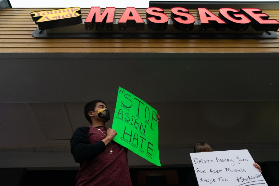 Jesus Estrella holds a sign of solidarity outside Youngs Asian Massage where four people were shot and killed on March 17, 2021 in Acworth, Georgia. (Elijah Nouvelage/Getty Images)