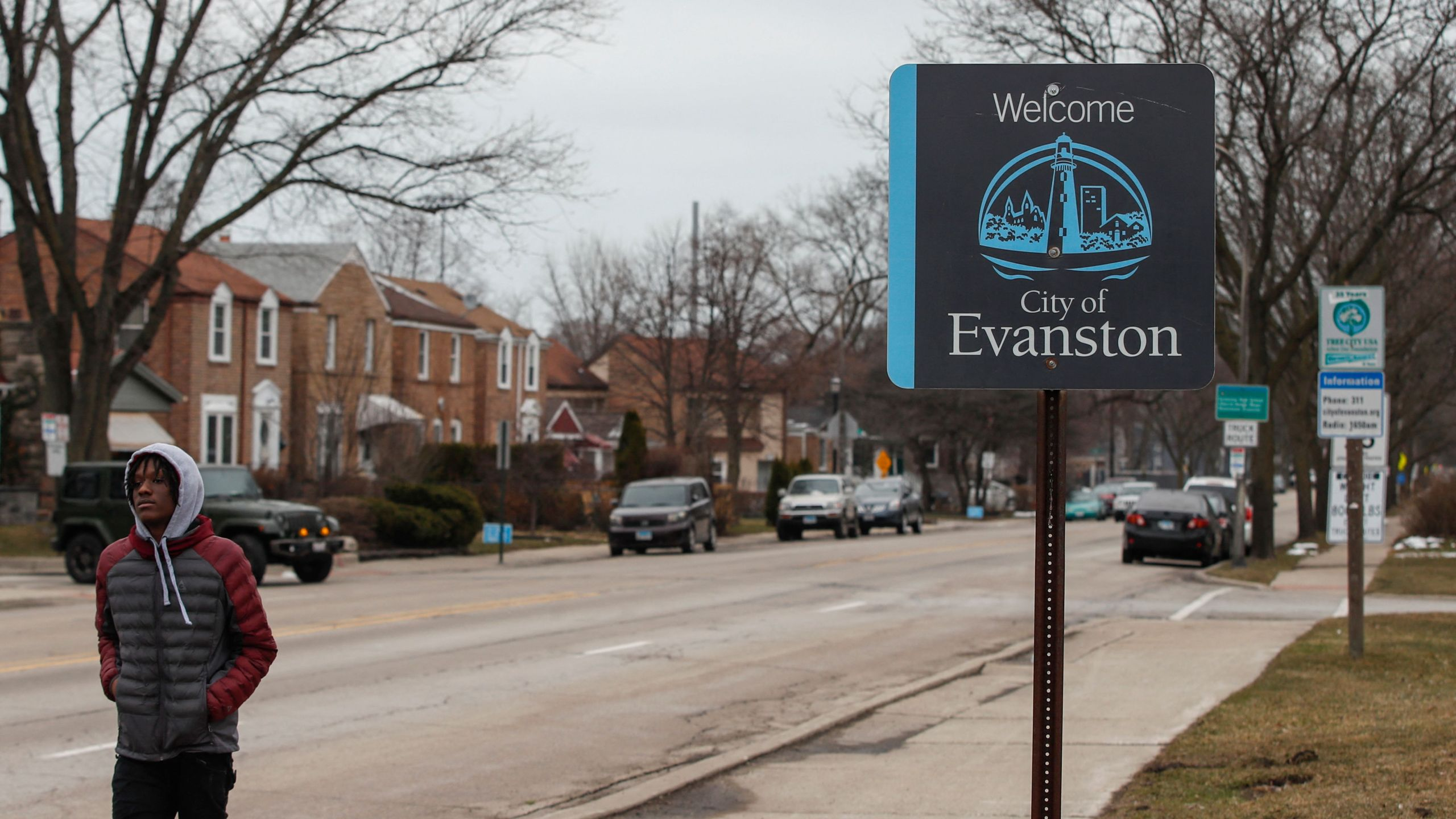 A man walks by a sign welcoming people to the city of in Evanston, Illinois, on March 16, 2021. (Kamil Krzaczynski /AFP / Getty Images)