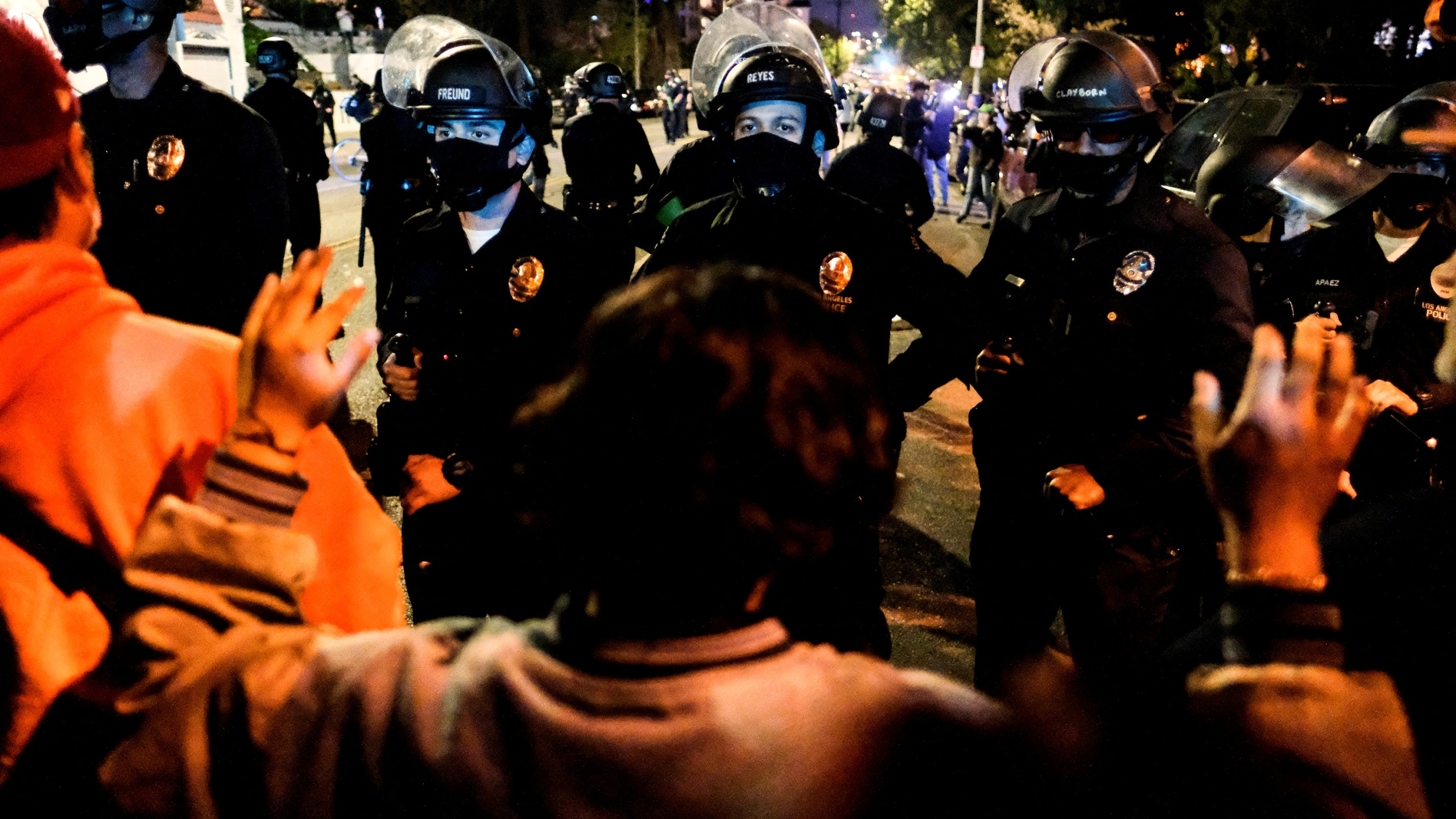 Activists and supporters of residents of a homeless encampment confront police at Echo Park Lake in Los Angeles late on March 24, 2021, ahead of a planned and announced clean-up of the encampment. (Ringo Chiu / AFP / Getty Images)